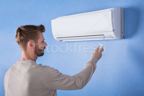 Rear View Of A Young Man Operating Air Conditioner Stock photo © AndreyPopov