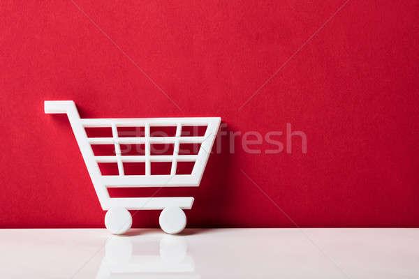 Közelkép fehér bevásárlókocsi dől piros fal Stock fotó © AndreyPopov