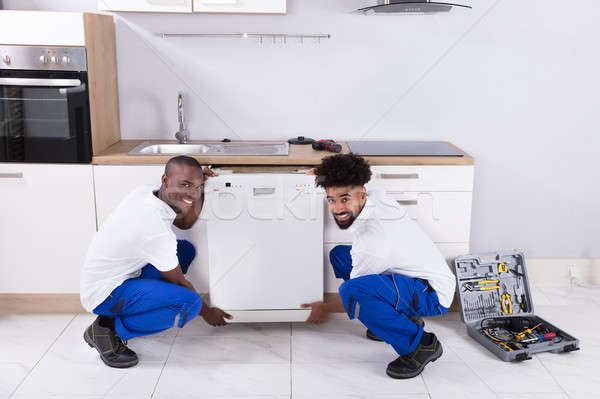 Two Handy Men Fixing The Dishwasher In The Kitchen Stock photo © AndreyPopov