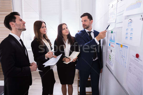 Businesspeople Looking At Charts Attached On White Board Stock photo © AndreyPopov