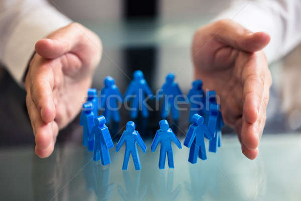 Businessperson Protecting Blue Human Figures Forming Circle Stock photo © AndreyPopov