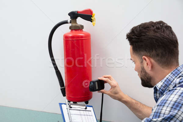 Technician Inspecting Fire Extinguisher Stock photo © AndreyPopov