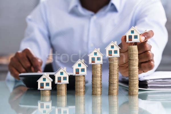 Businessperson Placing House Model On Coin Stacked Stock photo © AndreyPopov