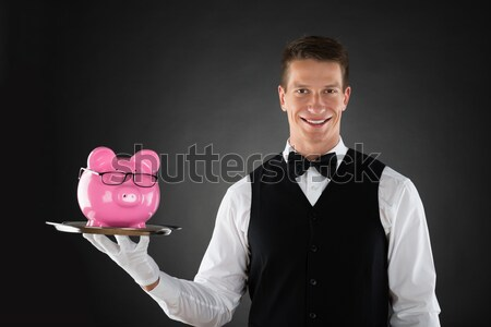 Portrait of a butler with piggybank Stock photo © AndreyPopov