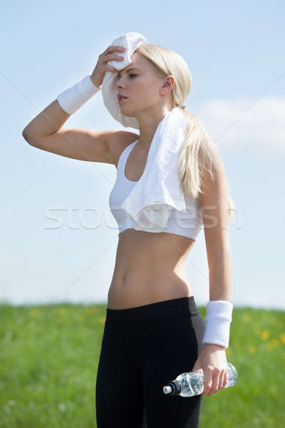 Tired Woman Wiping Face With Towel After Exercise Stock photo © AndreyPopov