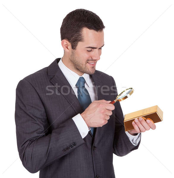 Businessman looking at gold bar through loupe Stock photo © AndreyPopov