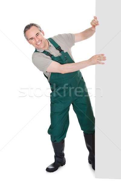 Happy mature gardener presenting empty banner Stock photo © AndreyPopov