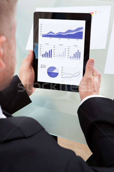 Businessman looking at graphs on his tablet Stock photo © AndreyPopov