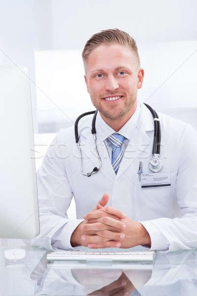 Lächelnd Arzt Berater Sitzung Schreibtisch Stethoskop Stock foto © AndreyPopov