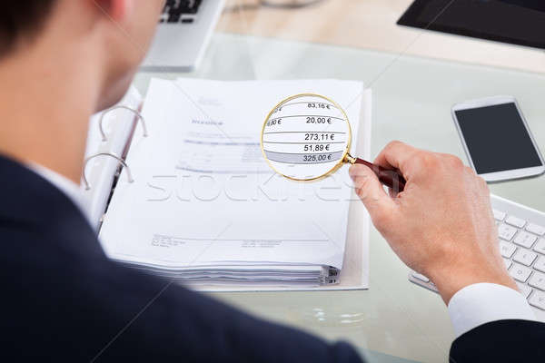Auditor Examining Invoice With Magnifier Stock photo © AndreyPopov