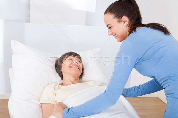 Caretaker Covering Senior Woman With Blanket Stock photo © AndreyPopov