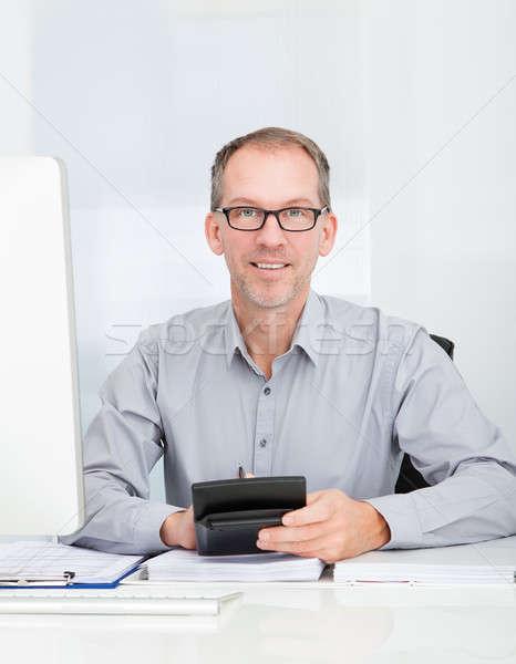 Biznesmen Kalkulator szczęśliwy posiedzenia komputera Zdjęcia stock © AndreyPopov