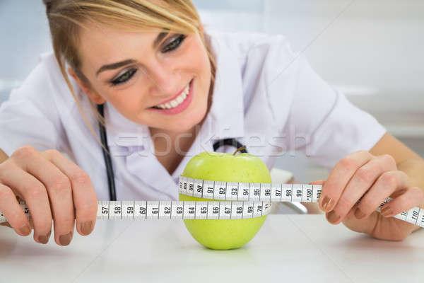 Female Dietician Measuring Green Apple Stock photo © AndreyPopov