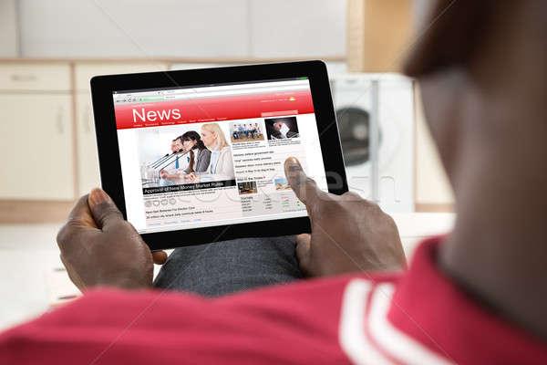 African Man Reading News On Digital Tablet Stock photo © AndreyPopov