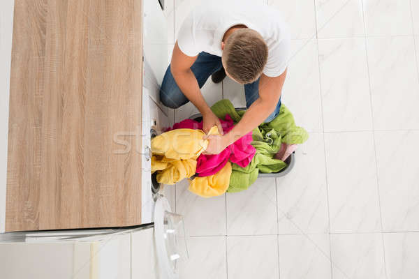 Man Putting Clothes In Washing Machine Stock photo © AndreyPopov