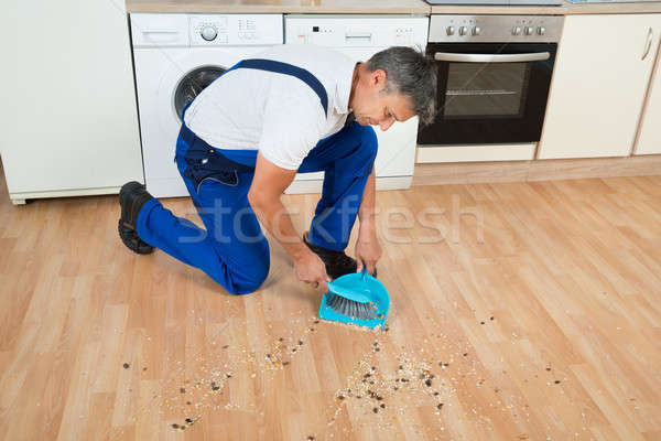 Janitor Sweeping Floor With Brush And Dustpan In Kitchen Stock photo © AndreyPopov