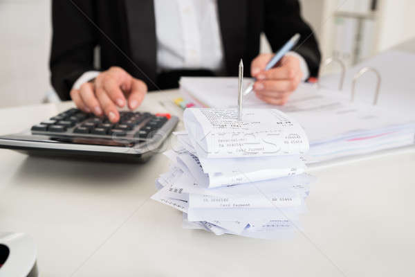 Receipts In Paper Nail With Businesswoman Working At Desk Stock photo © AndreyPopov