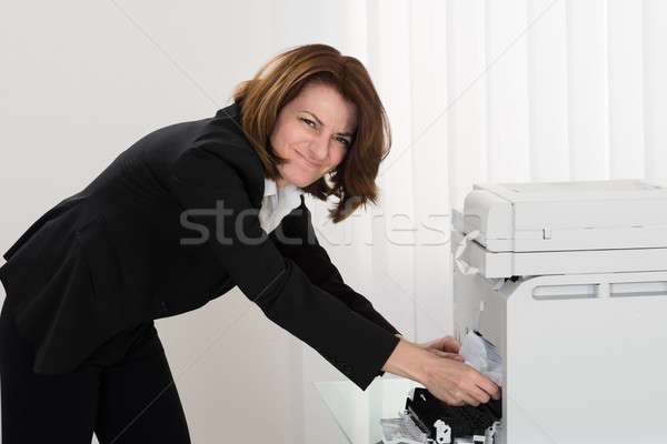 Businesswoman Removing Paper Stuck In Photocopy Machine Stock photo © AndreyPopov