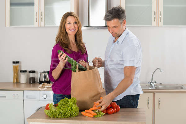 Couple Removing Vegetables From Grocery Bag Stock photo © AndreyPopov