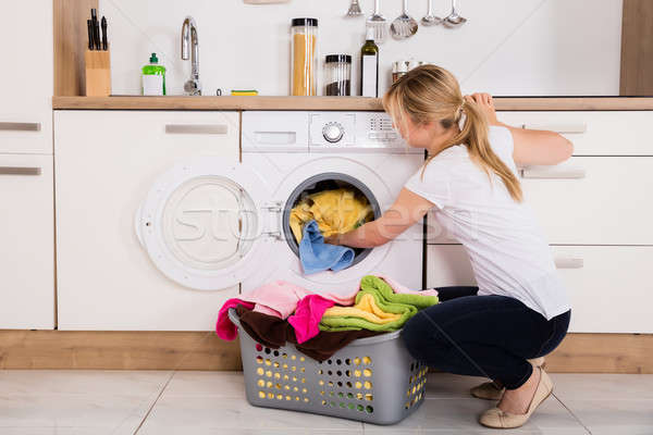 Woman Loading Clothes Into Washing Machine Stock photo © AndreyPopov