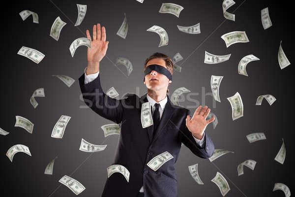 Blindfolded Businessman Standing Under Money Rain Stock photo © AndreyPopov
