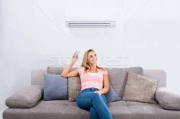Mujer acondicionador de aire control remoto jóvenes feliz sesión Foto stock © AndreyPopov