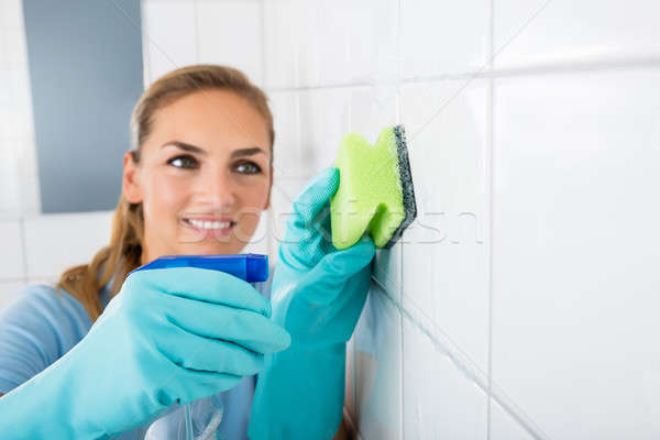 Stock photo: Smiling Woman Cleaning The White Tiled Wall