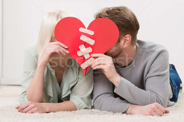 Couple Holding Red Paper Heart Fixed With Plaster Bandage Stock photo © AndreyPopov