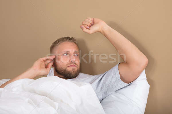 Unhappy Man Lying On Bed Stock photo © AndreyPopov