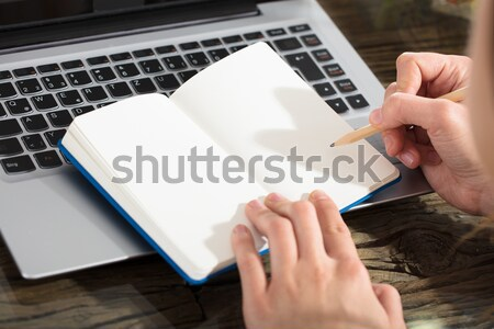 Businessperson Writing On Plain Notebook With Pencil Stock photo © AndreyPopov