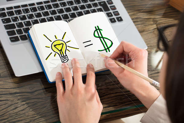Light Bulb And The Financial Gain Drawing On Notebook Stock photo © AndreyPopov
