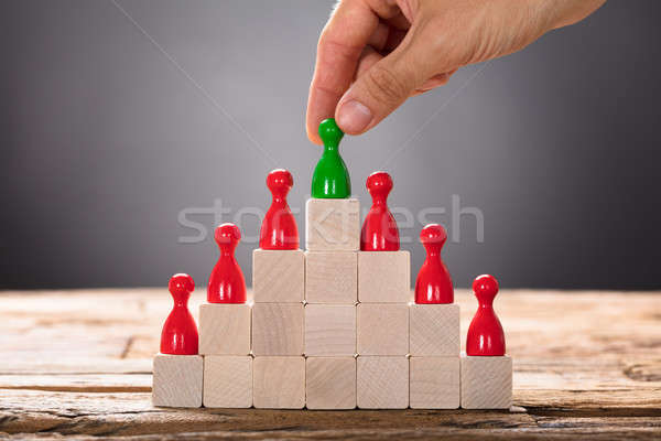 Hand Placing Green Pawn With Other Red Figurines On Blocks Stock photo © AndreyPopov