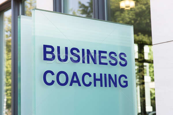 Business coaching sign on glass board outside building in city Stock photo © AndreyPopov