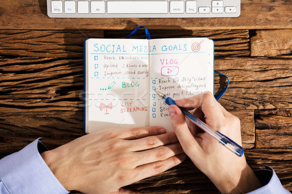 Person Making Social Media Plans On Notebook Stock photo © AndreyPopov