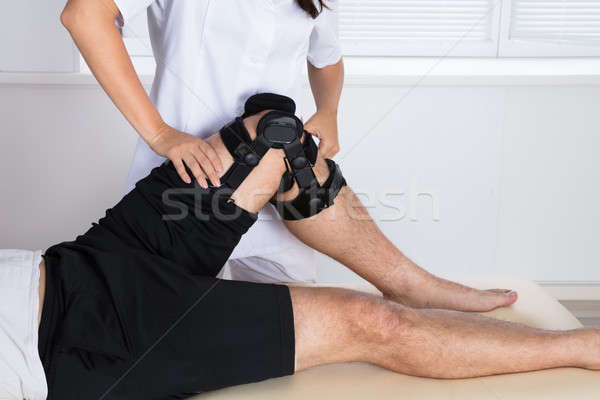 Physiotherapist Fixing Knee Braces On Man's Leg Stock photo © AndreyPopov