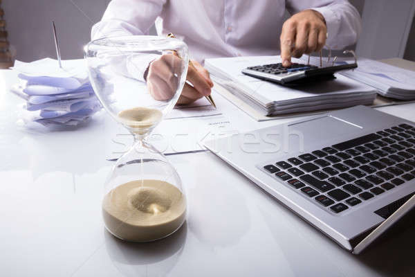 Businessman Calculating Invoice With Hourglass Stock photo © AndreyPopov