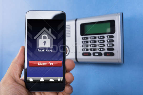 Hand Holding Smartphone For Disarming The System Stock photo © AndreyPopov