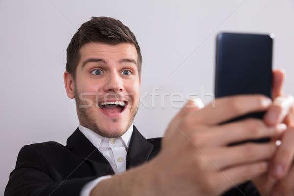 Stockfoto: Gelukkig · zakenman · naar · smartphone · jonge