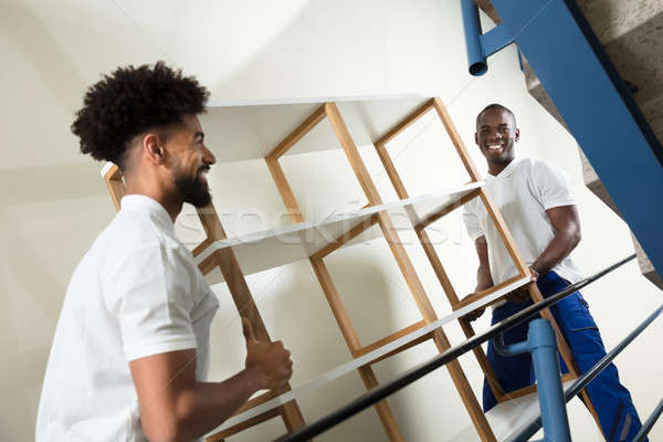 Two Male Movers Carrying The Empty Shelf At Home Stock photo © AndreyPopov