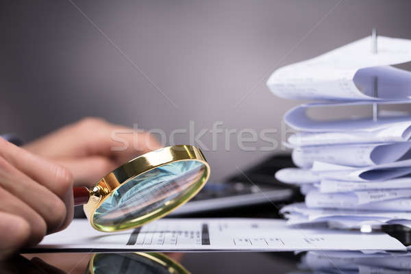 Stock photo: Businessperson Looking At Invoice Through Magnifying Glass