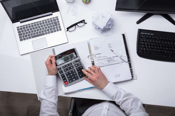 Elevated View Of Businessperson Calculating Invoice Stock photo © AndreyPopov