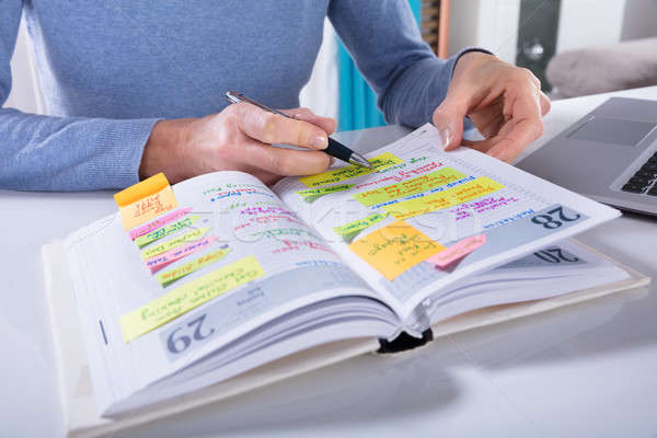 Woman Writing Schedule In Calendar Diary On White Desk Stock photo © AndreyPopov