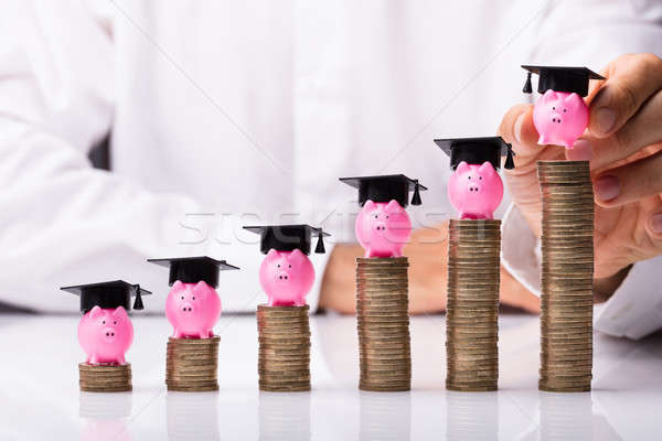 Person Placing Piggybank With Graduation Hat On Stacked Coins Stock photo © AndreyPopov
