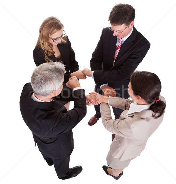 üzletemberek kéz a kézben csapatmunka csoport négy sokoldalú Stock fotó © AndreyPopov