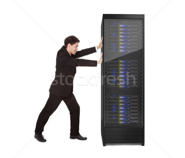 Businessman pushing server rack Stock photo © AndreyPopov