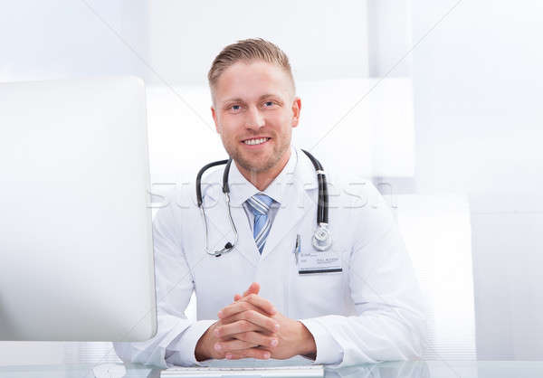 Sorridere medico consulente seduta desk stetoscopio Foto d'archivio © AndreyPopov