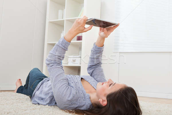 Woman Using Digital Tablet While Lying On Rug Stock photo © AndreyPopov