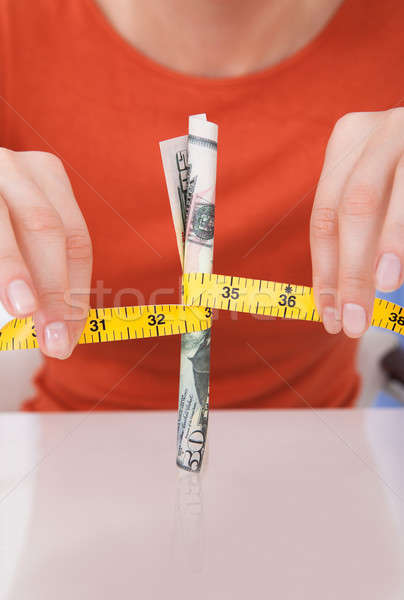 Woman Holding Measuring Tape Around 50 Dollar Bill Stock photo © AndreyPopov