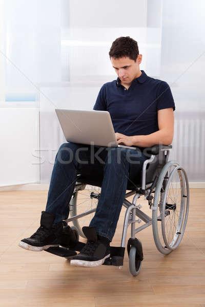 Upośledzony człowiek za pomocą laptopa wózek młodych Zdjęcia stock © AndreyPopov
