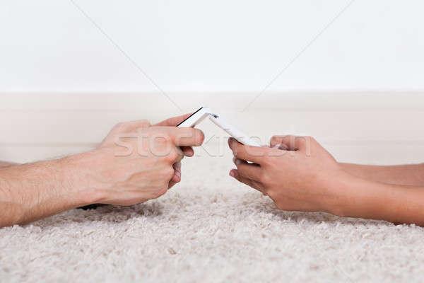 Kezek sms üzenetküldés okostelefonok szőnyeg kép otthon Stock fotó © AndreyPopov